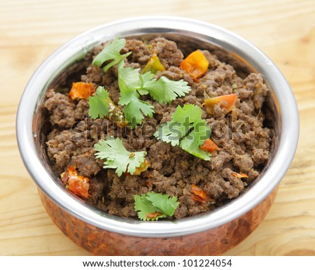 A minced beef or keema curry in a serving bowl, garnished with coriander leaves