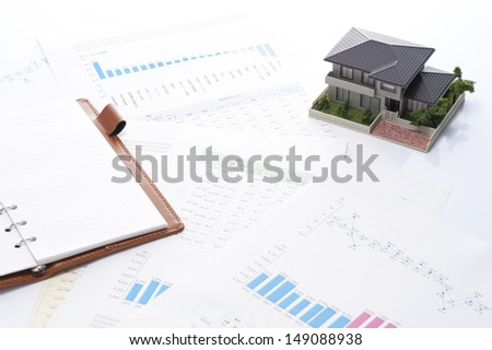 a miniature house and business document