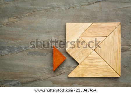 a missing piece in a square built from tangram pieces, a traditional Chinese puzzle game, slate rock background - stock photo