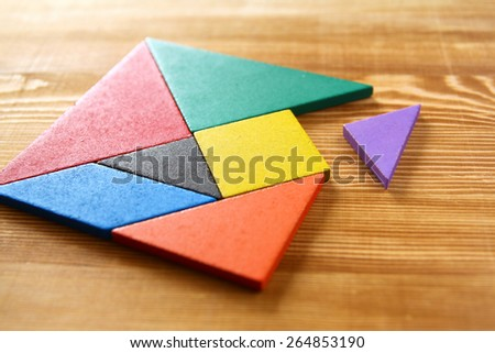 a missing piece in a square tangram puzzle, over wooden table. - stock photo