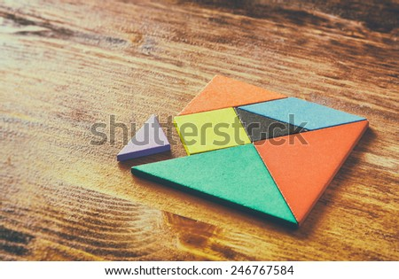 a missing piece in a square tangram  puzzle, over wooden table. faded style photo - stock photo