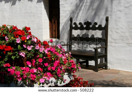 A mission-style bench with flowers in a plaza.