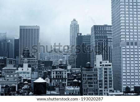A misty New York City landscape with various architectural styles in blue tones.
