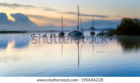 A misty sunrise at over boats moored at the quay in Christchurch in Dorset - stock photo