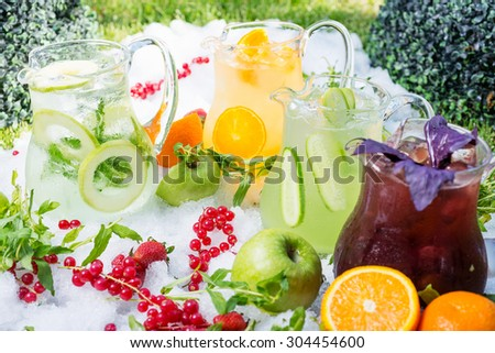 a mix of several bright colored delicious cold lemonade carafes of kiwi and orange and strawberry on the table with creative composition of ice berries oranges and mint. soft focus