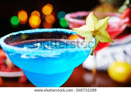 a mix of the two bright refreshing cocktails: blue margarita and strawberry daiquiri on a table in a restaurant with creative decoration of salt on the edge of the glass and berries. soft focus - stock photo