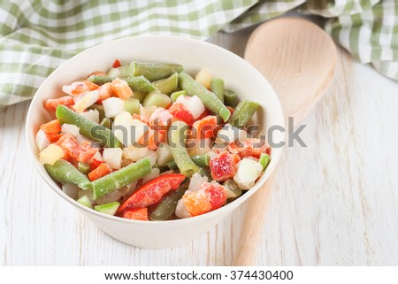 A mixture of assorted frozen vegetables in a bowl on white wooden table - stock photo