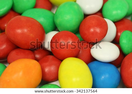 a mixture of colored chocolate candy in glaze background
