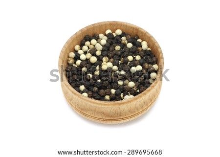 a mixture of grains of black and white pepper in a wooden bowl - stock photo