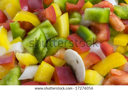 a mixture of green, red, yellow bell pepper, onion and mushrooms diced and ready for cooking or salad - stock photo