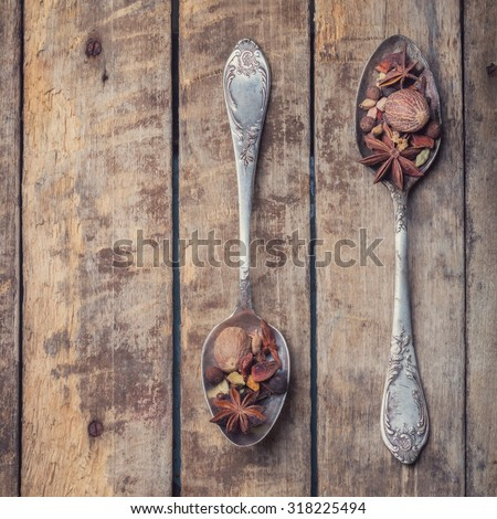 a mixture of herbs and spices for mulled wine in silver rustic spoons on textured wooden background. the view from the top. instagram style - stock photo