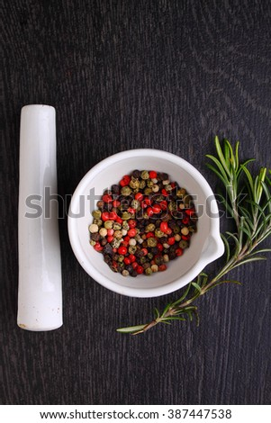 a mixture of peppers ( red, black , white ) in a white mortar with a sprig of rosemary - stock photo