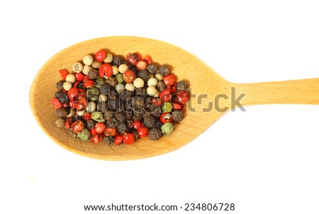 A mixture of seeds of pepper on a wooden spoon isolated on white background - stock photo