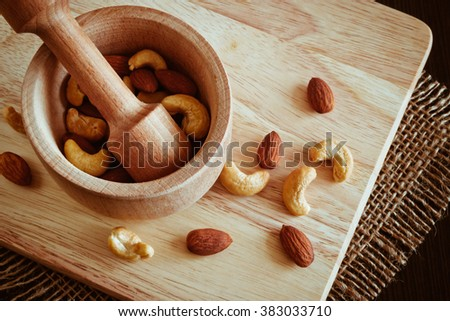 A mixture of various nuts in a wooden mortar and pestle made of hard wood on a cutting board