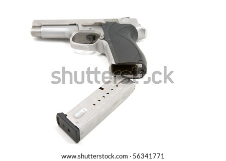A 9mm handgun magazine being loaded into the pistol - stock photo