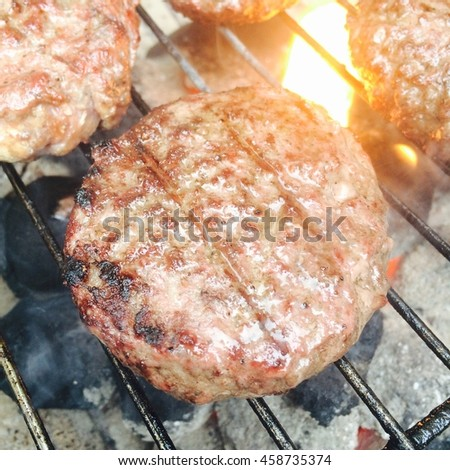 A mobile phone image fresh beef burger being grilled over a flaming barbecue - stock photo