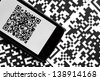 A mobile phone next to some QR codes printed on paper - stock photo