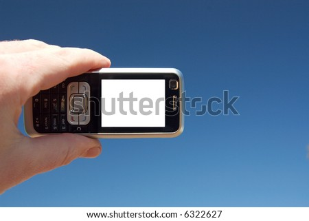 A mobile phone on a blue sky background. Copy-space on the phone screen. - stock photo