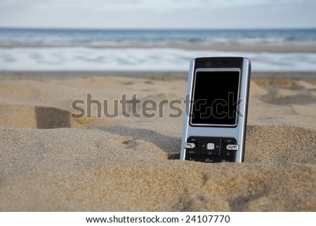 A mobile phone with blank black screen sits in the sand at the beach. - stock photo