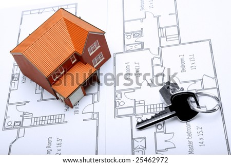 A model home and house key on architectural floor plans for an extension. - stock photo