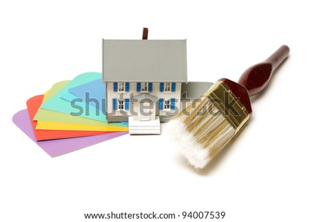 A model house, paintbrush, and color swatches come together for interior decorating concepts. - stock photo