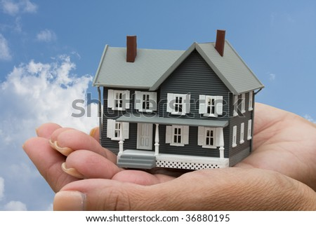 A model house sitting in hands on a sky background, mortgage help - stock photo