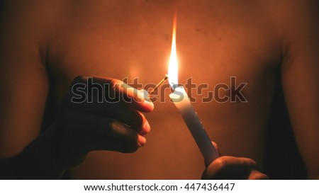 A model is lighting the candles (focus on candle)