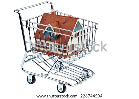 a model of a house in a shopping cart. symbol photo for home purchase. - stock photo