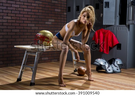 A model posing in a locker room environment with american football equipment.  - stock photo