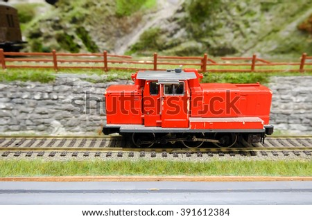 A model railroad steam locomotive in red, selective focus (slightly warm tone) - stock photo