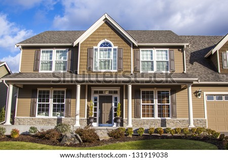 A modern American house front entrance with green grass on front - stock photo