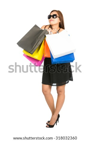 A modern Asian woman shopaholic wearing stylish sunglasses and chic black dress hugs department store shopping bags to her chest while looking up and daydreaming. Isolated on white background - stock photo