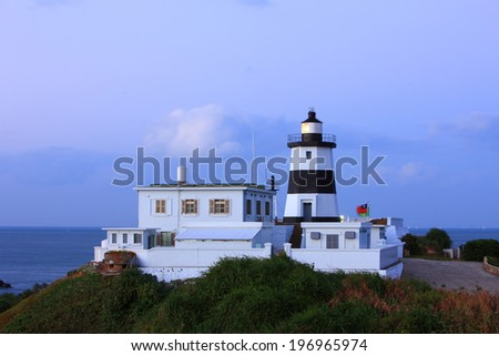 A modern black and white lighthouse with a light station next to the ocean.