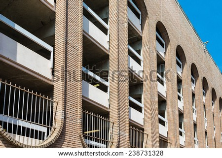 A modern brick parking garage with curved windows - stock photo