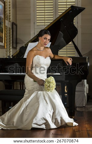 A modern bride poses indoors with a grand piano - stock photo