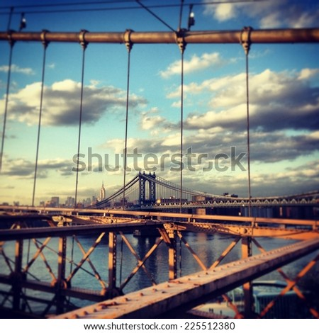 A modern bridge in the distance viewed through the bars of an old rusty bridge. - stock photo