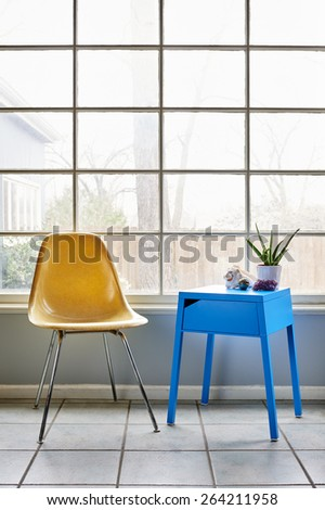 a modern chair and table in a well lit room - stock photo