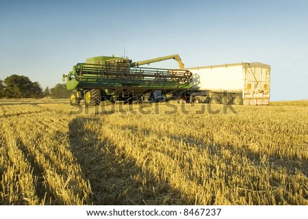 A modern combine harvester emptying grain into a truck