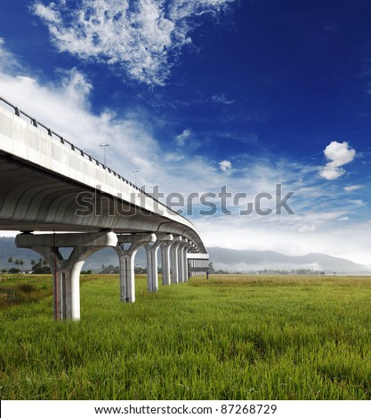 A modern concrete elevated motor express highway spanning across a rural tropical rice field towards a mountain range, with a cloudy blue sky. - stock photo