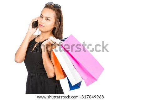 A modern, cute Asian female shopper wearing a stylish black dress, sunglasses holds many colorful department store shopping bags while talking on her cell phone looking at the camera. Half Horizontal
