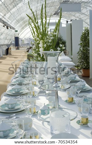 A modern decorated wedding table with large vase and white flowers. - stock photo