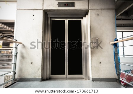 a modern elevator in the store, closed doors - stock photo