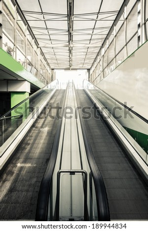 a modern escalator in a mall or an airport  ending in the bright light of the sun
