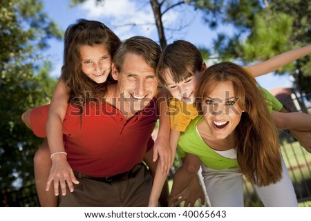 A modern family of father, mother, daughter and son playing together and having fun doing piggy back in a park - stock photo