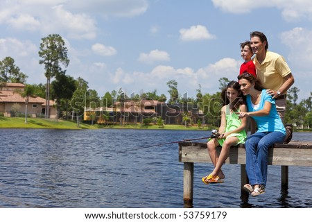 A modern family of mother, father, children, son and daughter fishing in a lake off a jetty on a sunny day - stock photo