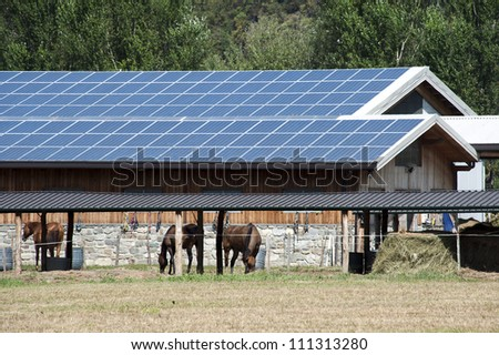 A modern farm with solar panels on the roof - stock photo