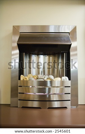 A modern fireplace with a metal surround - stock photo