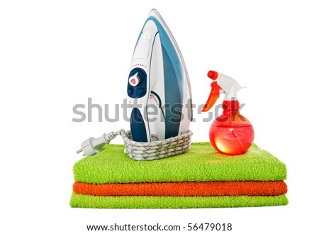 A modern flat iron and a spray with the pressed multicolored towels isolated on the white background - stock photo