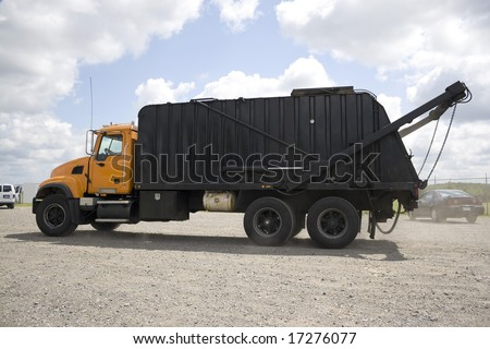 A modern garbage truck over a bright blue sky. - stock photo