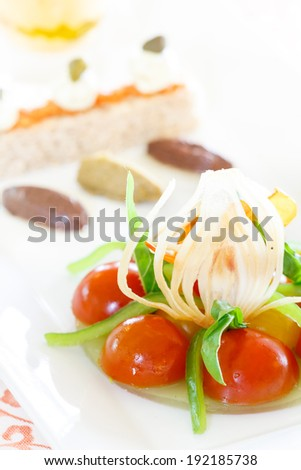 A modern Greek salad with cherry tomatoes, cucumber jelly, confit onions, olive oil - stock photo